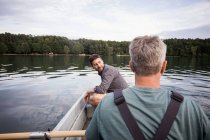 Caucasian men are fly fishing in boat on a river. — Stock Photo