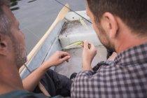 Zwei Männer pflücken eine Fliege von einem Fliegenfischergerät in einem Boot auf dem Fluss. — Stockfoto