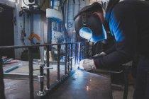 Un fabbro indossa ingranaggio di sicurezza ed è una costruzione in metallo nella bottega di un fabbro di saldatura. — Foto stock