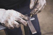 Коваль вживає заходів на шматок металу в майстерні. — стокове фото