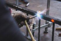 Коваль в шкіряний фартух використовує різання факелом у свою майстерню. — стокове фото