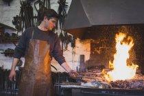 Un herrero está calentando una barra de hierro en un taller . - foto de stock