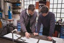 Deux forgerons prennent des mesures, effectuer des calculs et planifier une journée de travail dans l'atelier du forgeron. — Photo de stock