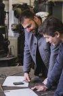 Два ковалі вжиття заходів, робити розрахунки та графіку робочих днів у семінар ковальські. — стокове фото