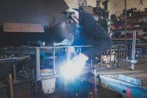 Коваль носить захисне спорядження і зварювання металоконструкцій в майстерні в metalsmith. — стокове фото