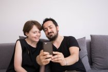 A young couple is doing selfies with a smart phone while chilling out on the couch during weekend. — Stock Photo
