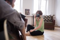 A young woman is taking pictures of her boyfriend in the living room. — Stock Photo
