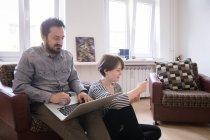 Una joven pareja es navegar por Internet y comprobar el teléfono inteligente mientras se relaja en la sala de estar - foto de stock