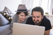 A young couple is browsing the Internet while relaxing on the couch in the living room. — Stock Photo