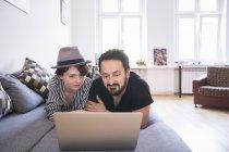 Ein junges Paar ist das Surfen im Internet während Sie gemütlich auf der Couch im Wohnzimmer — Stockfoto