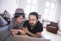 Un jeune couple est la navigation sur Internet tout en vous relaxant sur le canapé dans le salon — Photo de stock