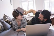 A young couple is streaming TV-series on the computer while having fun on the couch in the living room. — Stock Photo
