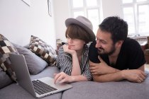 A young couple is streaming TV-series on the computer while relaxing on the couch in the living room. — Stock Photo