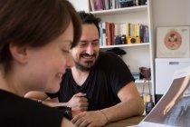 Una giovane coppia leggere il giornale al tavolo della colazione durante un fine settimana a casa — Foto stock