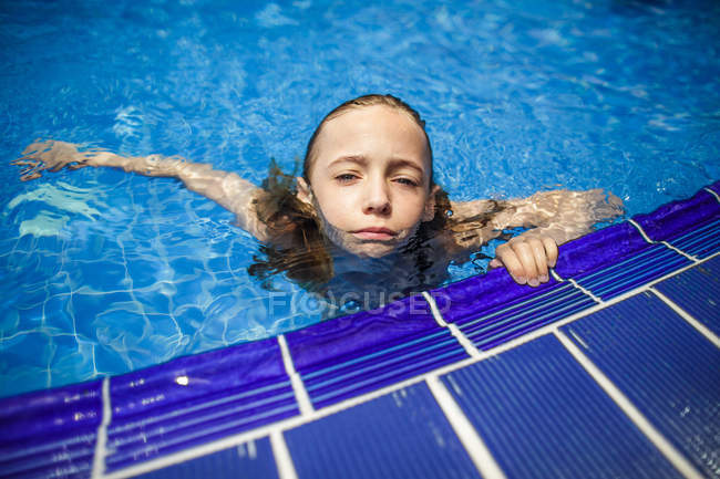 A thoughtful girl is relaxing by the side of a swimming pool. — Stock Photo