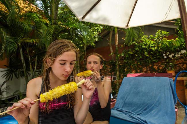 Dos hermanas están comiendo palitos de maíz a la parrilla en una zona de piscina durante unas vacaciones en Tailandia . - foto de stock