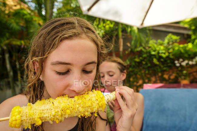 Duas irmãs estão comendo palitos de milho grelhados em uma área de piscina durante umas férias na Tailândia . — Fotografia de Stock