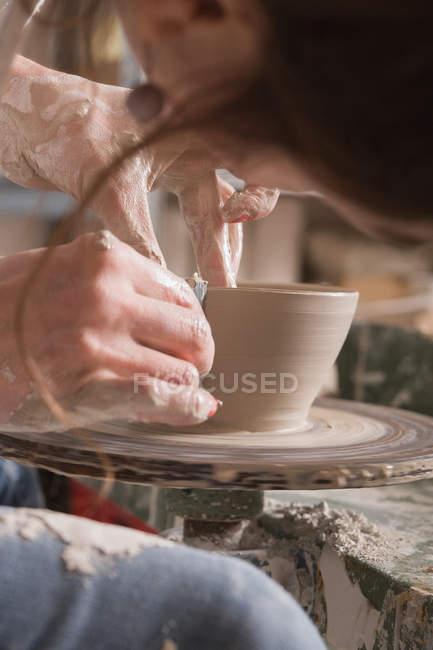 Close up de uma mulher moldando argila de cerâmica em uma roda de cerâmica em uma oficina de cerâmica . — Fotografia de Stock