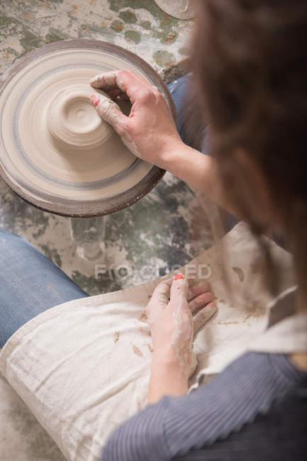 Mulher caucasiana está moldando argila de cerâmica em uma roda de cerâmica em uma oficina de cerâmica . — Fotografia de Stock