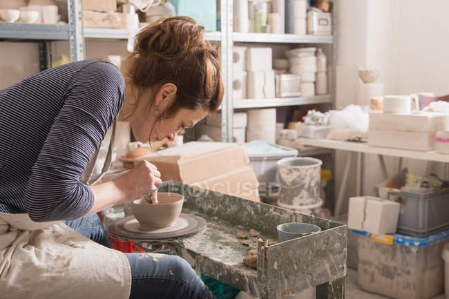 Kaukasierin formt in einer Keramikwerkstatt auf einer Töpferscheibe Ton. — Stockfoto