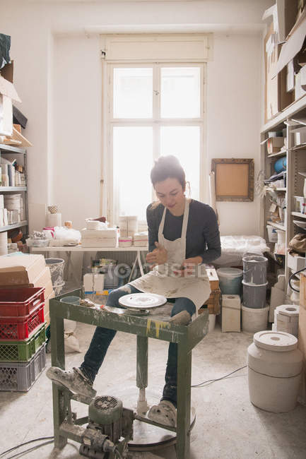 Caucasian woman is shaping pottery clay on a pottery wheel in a ceramic workshop. — Stock Photo