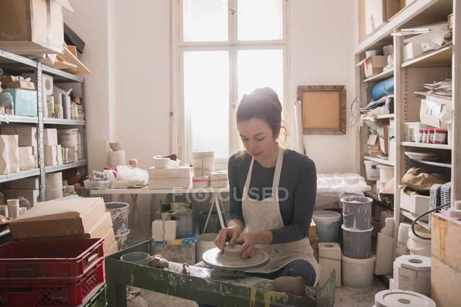 Кавказка формирует глину на гончарном круге в керамической мастерской . — стоковое фото
