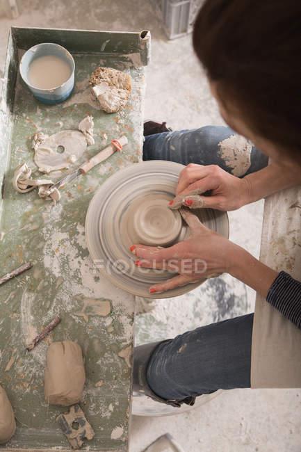 Um artista cerâmico moldando argila de cerâmica em uma roda de cerâmica em uma oficina de cerâmica . — Fotografia de Stock