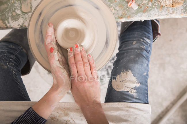 A ceramic artist shaping pottery clay on a pottery wheel in a ceramic workshop. — Stock Photo