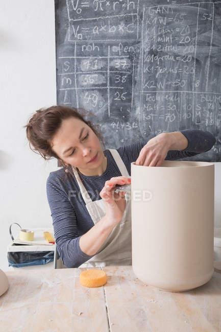 Un artista della ceramica sta mettendo i tocchi finali ad un'urna di ceramica in un laboratorio di ceramica . — Foto stock