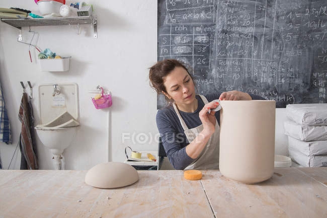 A ceramic artist is putting the finishing touches to a ceramic urn in a ceramic workshop. — Stock Photo