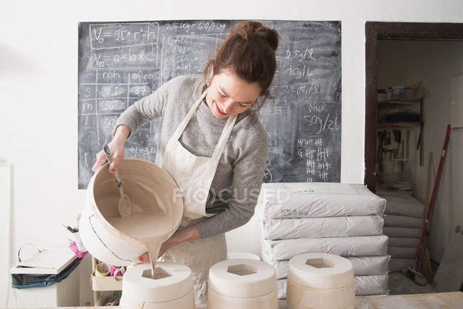 A ceramic artist is slipcasting ceramics in a pottery workshop. — Stock Photo