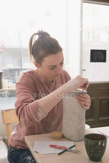 A ceramic artist is putting the finishing touches to a ceramic pitcher in a pottery workshop. — Stock Photo