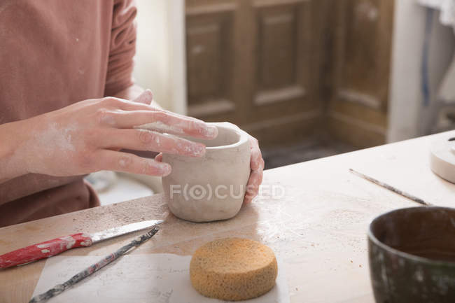 A ceramic artist is putting the finishing touches to a ceramic cup in a pottery workshop. — Stock Photo
