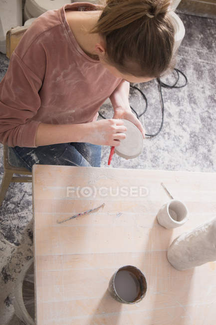 A ceramic artist is putting the finishing touches to a ceramic piece in a pottery workshop. — Stock Photo