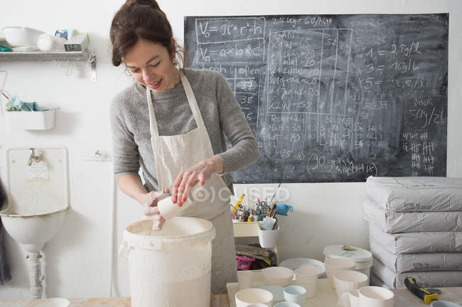 A ceramic artist is glazing ceramics in a pottery workshop. — Stock Photo