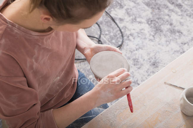 Un artista cerámico está dando los toques finales a una pieza de cerámica en un taller de cerámica . - foto de stock