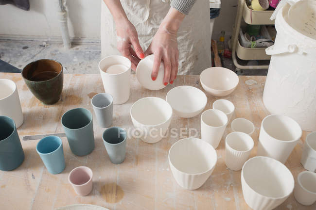 A ceramic artist is putting the finished ceramic products on the table in a pottery workshop. — Stock Photo