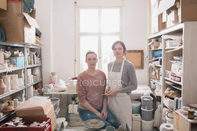 Two ceramic artists portrayed in their pottery workshop. — Stock Photo