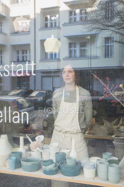 Un produttore di ceramica visto attraverso la finestra del suo laboratorio di ceramica . — Foto stock
