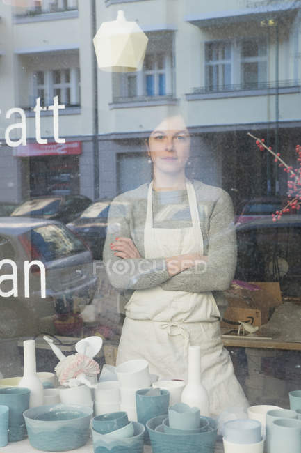 A ceramic maker seen through the window of her pottery workshop. — Stock Photo