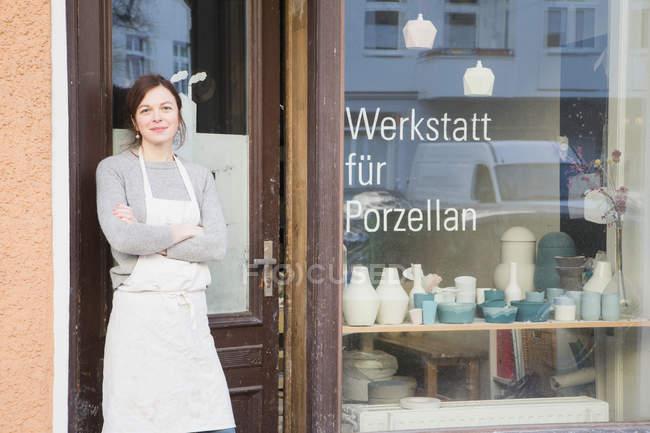A ceramic maker portrayed outside her pottery workshop. — Stock Photo