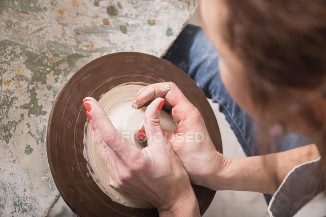Close up da mão de uma mulher moldando argila de cerâmica em uma roda de cerâmica em uma oficina de cerâmica . — Fotografia de Stock
