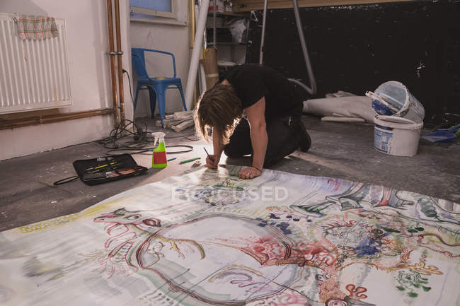 Creative male artist working in his workshop with painting on floor — Stock Photo