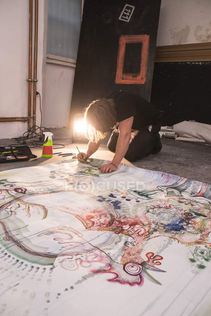 Creative male artist working in his workshop with paper on floor — Stock Photo