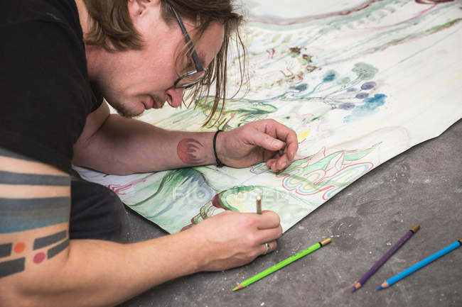 Creative male artist working in his workshop while lying over paper — Stock Photo