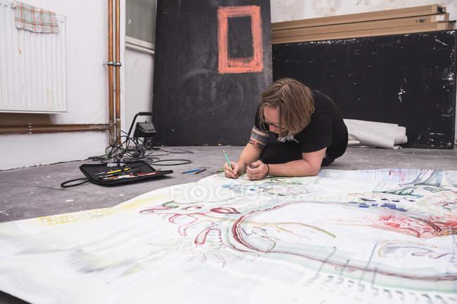 Kreativer männlicher Künstler arbeitet in seiner Werkstatt, während er über Papier liegt — Stockfoto