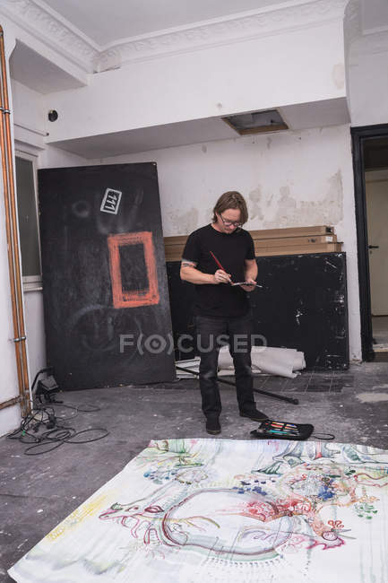 Creative male artist working in his workshop with brush in hand — Stock Photo