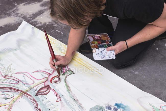 Творческий мужчина-художник, работающий в мастерской, стоя на коленях у бумаги — стоковое фото