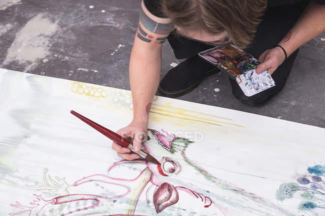 Творческий мужчина, работающий в мастерской с кистью в руке — стоковое фото