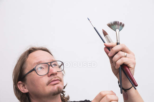 Portrait of male artist working in his workshop and looking on brushes  in hands — Stock Photo